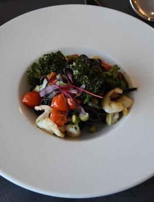 Świeże Tagliolini – makaron barwiony sepią w maślano-szparagowym sosie z krewetkami, pomidorkami cherry, ricottą oraz chipsem z jarmużu